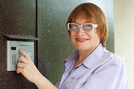 Mature woman pushing button of house intercom Stock Photo - 9854580