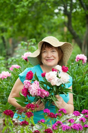 pion: Happy mature woman in peony plant at garden