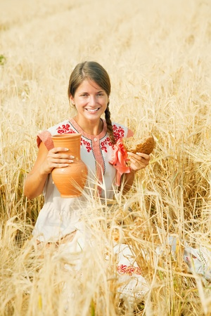 Girl in traditional clothes with bread at cereals field photo