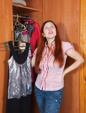 Young woman standing at wardrobe. She thinking what get dressed. photo