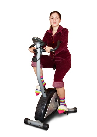 Young woman in  sportswear exercising on exercise bike. Isolated over white background photo