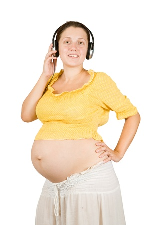 Pregnant woman with headphones. Isolated over white  photo
