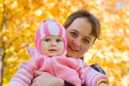 Happy mother with little baby outdoor in autumn photo