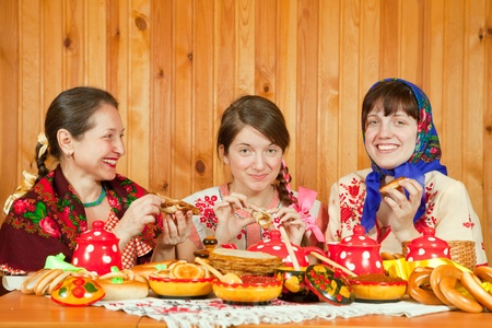 Women in traditional  clothes eating pancake with caviare during  Pancake Week Stock Photo - 9854815