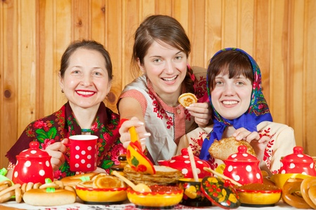 Women in traditional  clothes eating pancake with caviare during  Shrovetide Stock Photo - 9854816