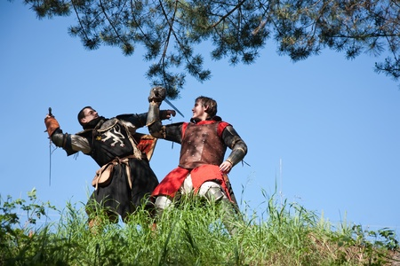 sword fighting: Two knights in armor is fighting  against blue sky