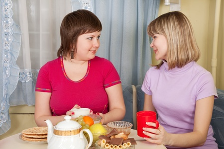 Girls  drinks tea and talking in the kitchen photo