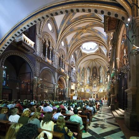 montserrat: SANTA MARIA DE MONTSERRAT, SPAIN - 9 APRIL: Worshipers during worship in catholic church on April 9, Montserrat mountain, Spain. Santa Maria de Montserrat in  greatest monastery of Catalonia