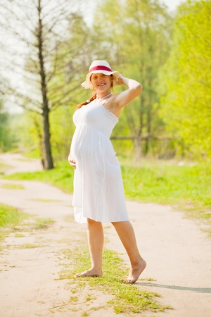 Portrait of 6 months pregnant woman in summer day photo