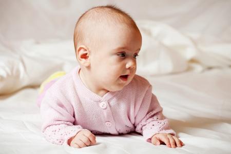 babygro: 5 months baby girl laying on white sheet