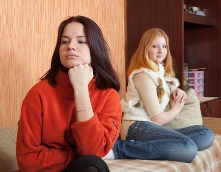 Two sad girls having quarrel at home photo
