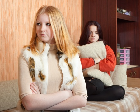 Two sad girls having quarrel at home photo
