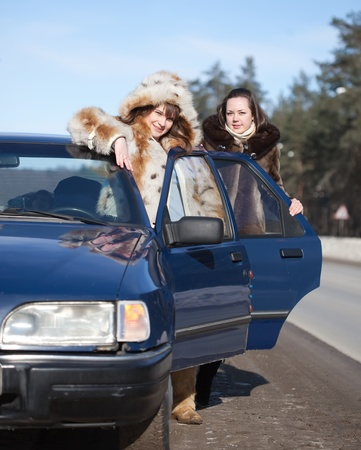 Two young women with car in winter day photo