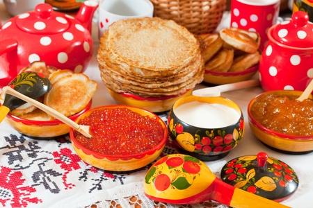 Pancake with red caviar and tea during  Pancake Week  photo