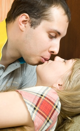 young couple kissing on sofa at home photo