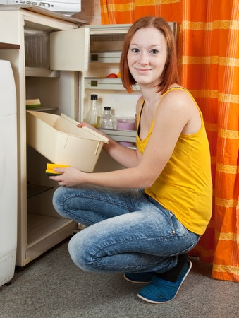 icebox: Young woman  defrosting the refrigerator at her kitchen
