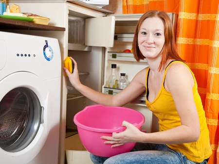 icebox: Young woman  cleaning the refrigerator at her kitchen