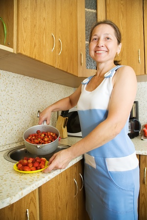 Woman in the kitchen washing red strawberry photo
