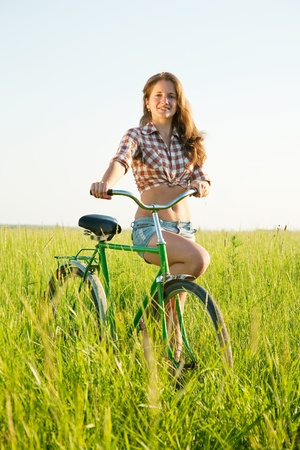 beautiful girl riding bicycle in grass field photo