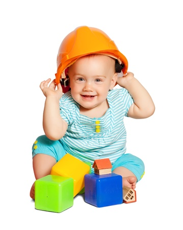 Toddler in hardhat plays  with toy blocks over white background photo