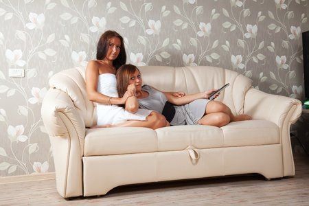 Two mid adult women look cinema laying on sofa photo
