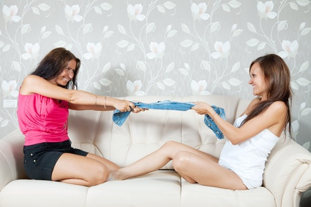 Happy women dividing clothes on sofa in livingroom at home Stock Photo - 9977251