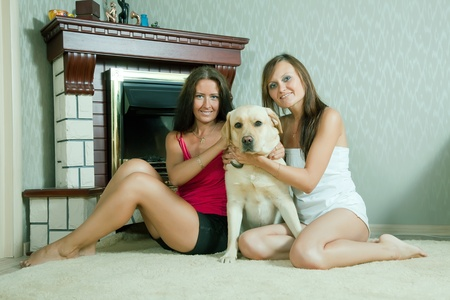 Two mid adult women with  labrador retriever in home interior photo