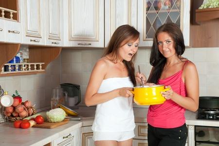 mujeres cocinando: Dos a mediados de mujeres adultas de cocina en ellos cocina