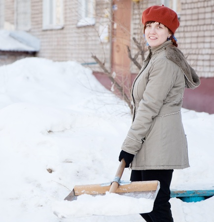 Girl throwing snow  with shovel in snowy street photo