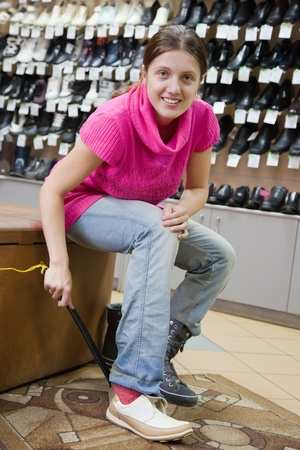 admixture: Girl chooses wintry shoes at shoes shop