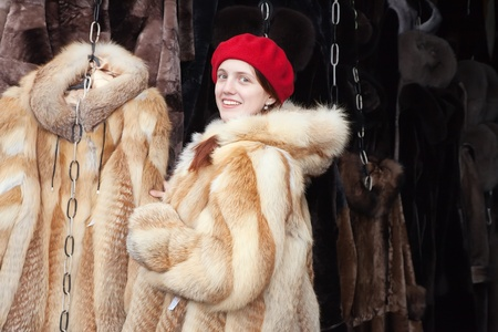 furskin: Woman  chooses fur coat at fashionable shop