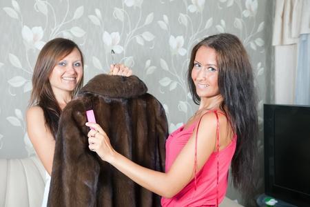 bontjas: Twee vrouwen reinigen bontjas met een garde bezem thuis