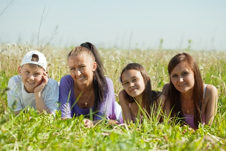 Two happy  women with teens laying in grass Stock Photo - 10132470