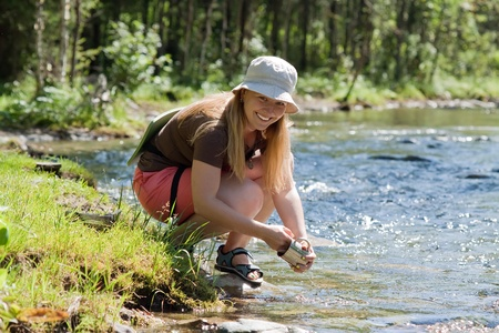 Female tourist washing utensil in mountains river  photo