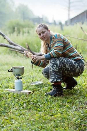 Girl making  coffee on gas burner at mountains  photo