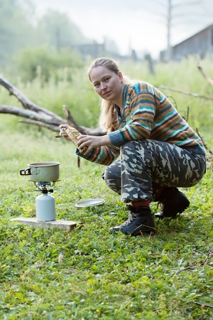 Girl making  coffee on gas burner at mountains  photo