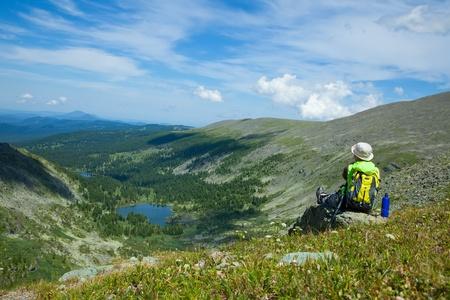 Achteraanzicht van de vrouw zittend op rots bij bergtop