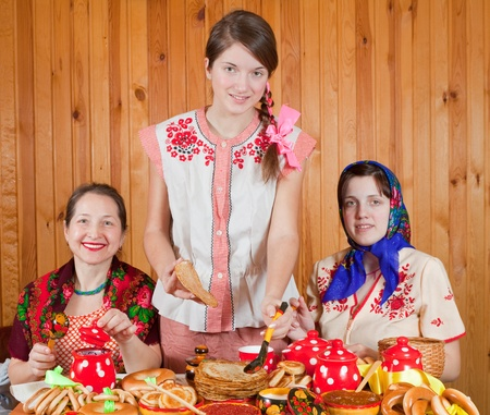 sudarium: Women in traditional  clothes eating pancake during  Shrovetide