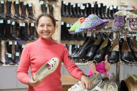 Mature woman shopping at fashion shoe store photo