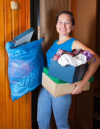 sweeps: Mature woman tossing out the garbage at home Stock Photo