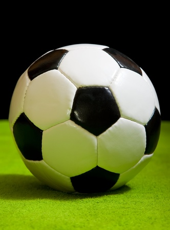 classic soccer ball on green over black photo