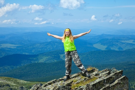 altai mountains:  woman standing on  mountain peak with raised hands  at mountain peak