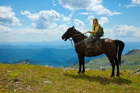 Turista femenina a caballo en las montañas Foto de archivo