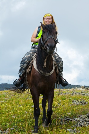 Female rider on horseback at mountains photo