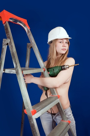 Topless girl in hard hat with drill near scaling-ladder photo