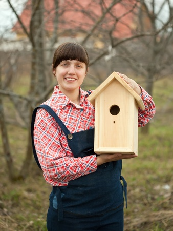 Woman with new birdhouse at garden photo