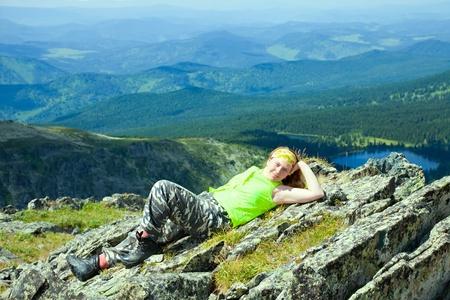 alpinist: Female tourist resting at mountain peak