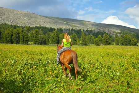 female rider riding a horse bareback at mountains  photo