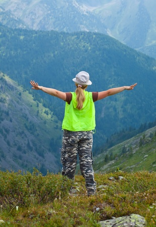 Woman standing on mountain peak and looking to valley below photo