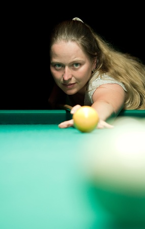Woman aiming for billiard table over black background photo